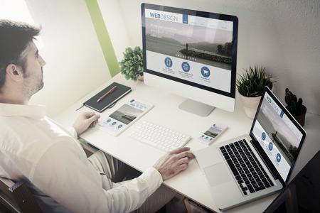 empleado de oficina: hombre que trabaja con dispositivos con un diseño web adaptable. Todos los gráficos de la pantalla se componen.