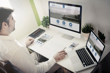 web screen: man working with devices with responsive web design. All screen graphics are made up.