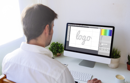 graphic designer designing a  on computer. All screen graphics are made up. Stock Photo