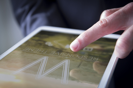 finger touches digital tablet showing responsive website template on screen Stock Photo