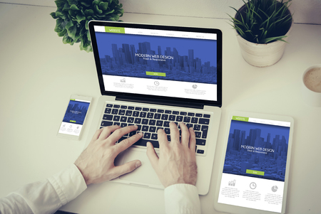 web portal: business, technology and responsive design concept: hands writing on a laptop with phone and tablet fresh modern design