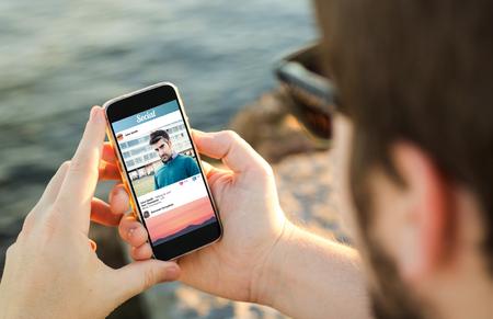 man aan de kust met behulp van zijn smartphone. Alle screen graphics zijn opgebouwd. Stockfoto