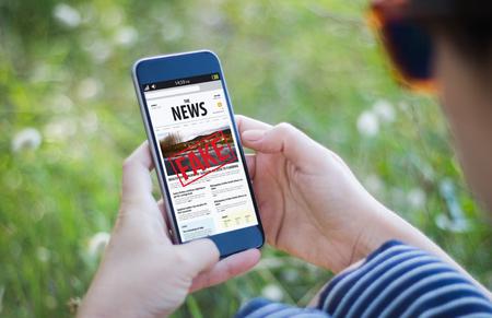 niña en la hierba sosteniendo su teléfono inteligente y leyendo noticias falsas. Todos los gráficos de pantalla están compuestos.