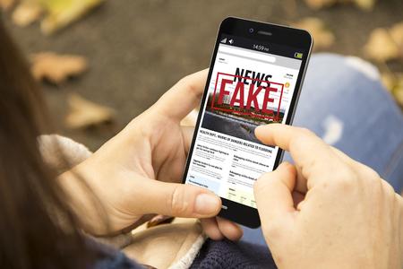 Media technologie en moderne levensstijl concept: jonge vrouw met smartphone lezen nep nieuws in het park Stockfoto