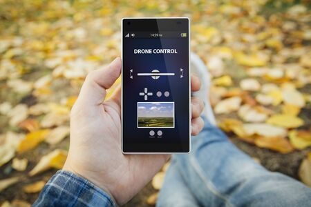 man made: man in the park controlling a drone with smartphone. All screen graphics are made up. Stock Photo