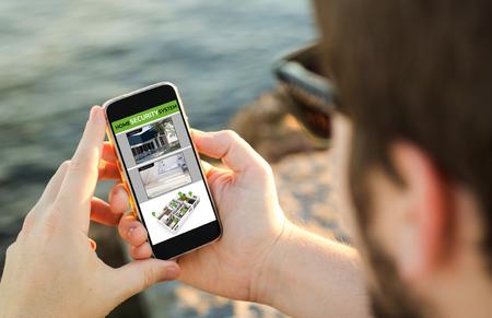 Hombre en la costa usando su teléfono inteligente para monitorear webcams. Todos los gráficos de la pantalla se componen. Foto de archivo - 80316632