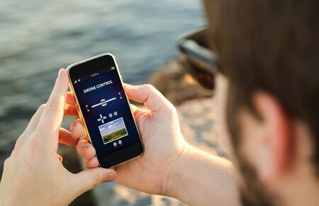 man on using drone control app on his smartphone. All screen graphics are made up. Stock Photo