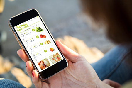 close-up view of young woman shopping groceries on online supermarket with her mobile phone. All screen graphics are made up.