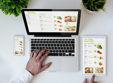 office tabletop with tablet, smartphone and laptop showing cool responsive online supermarket website 스톡 콘텐츠