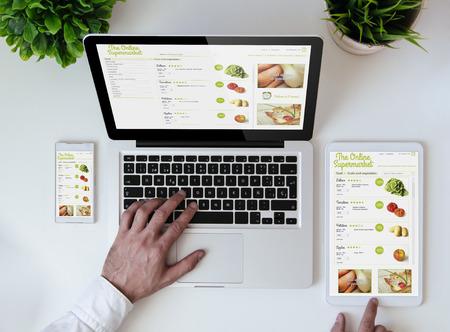 office tabletop with tablet, smartphone and laptop showing cool responsive online supermarket website Foto de archivo