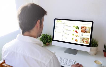Man shopping groceries online on computer Foto de archivo