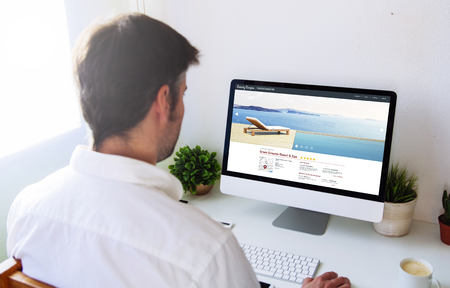 hotel reviews: Man browsing resort and spa website on computer