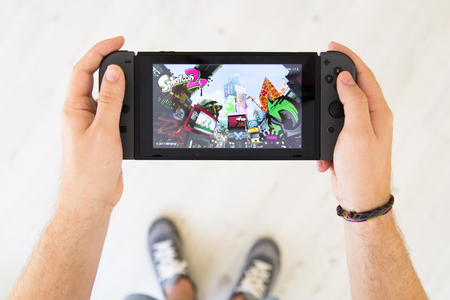 GIJÓN, SPAIN - AUG 10, 2017: Man playing Splatoon 2 on a Nintendo Switch, a video game console developed by Nintendo