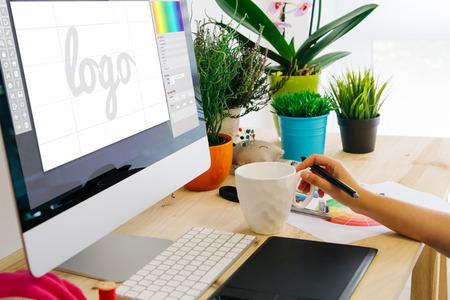 Grafikdesigner, der Stifttablette verwendet, um ein Logo zu entwerfen. Alle Bildschirmgrafiken werden zusammengestellt.