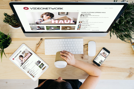overhead view of woman drinking coffee and browsing video network Foto de archivo