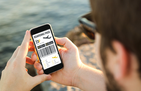 man on the coast using his smartphone showing boarding pass. All screen graphics are made up.