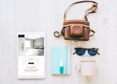 overhead hotel reservation website on tablet screen  with essential vacation items Stock Photo