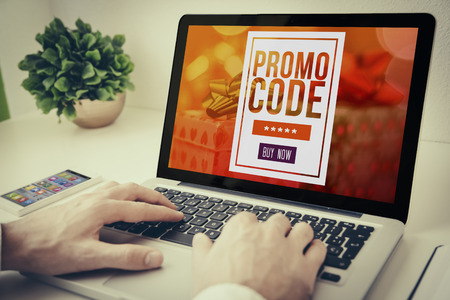 Hands using laptop on desktop with promo code