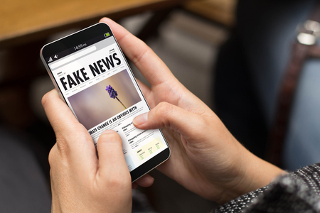 information concept: girl using a digital generated phone with fake news on the screen. All screen graphics are made up.