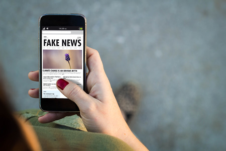 Top view of woman walking in the street using her mobile phone with fake news. All screen graphics are made up. Stock Photo