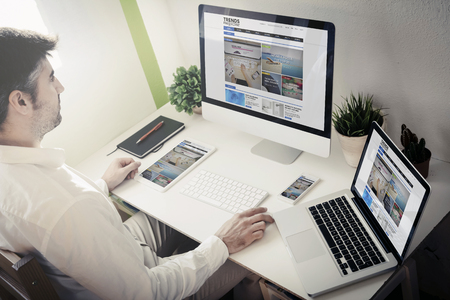 man surfing internet with devices with blog magazine website. All screen graphics are made up. Banco de Imagens