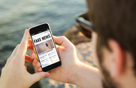 man aan de kust met behulp van zijn smartphone om nep nieuws te lezen. Alle schermafbeeldingen zijn samengesteld. Stockfoto