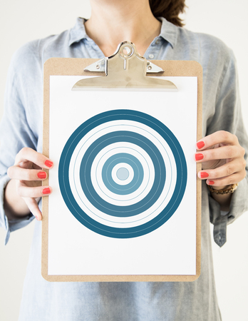woman holding a clipboard with bullseye Stock Photo