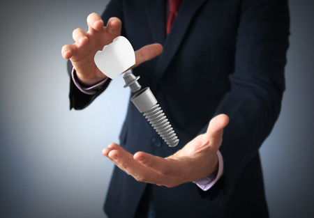 dental insurance or care concept: dentalprosthesis on the hand of a businessman Stock Photo