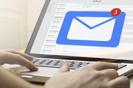 Online-Business-Konzept: Mann mit einem Laptop mit E-Mail auf dem Bildschirm. Bildschirmgrafiken werden erstellt. Standard-Bild