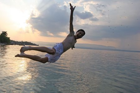 joyfully: Boy joyfully jumping in the lake at sunset Stock Photo