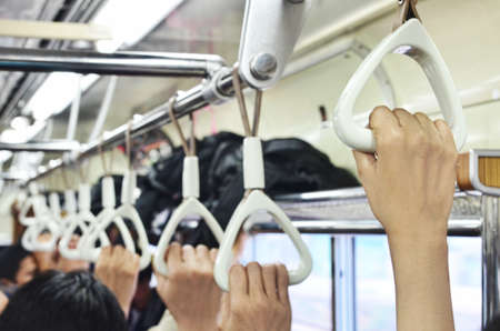 Passengers hands holding handrails in commuter line