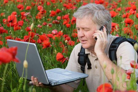Photographer speaking on mobile in poppy field Stock Photo - 3129036