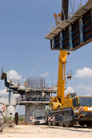 Crane lifting a metal frame to place it on pillar guided by a worker photo