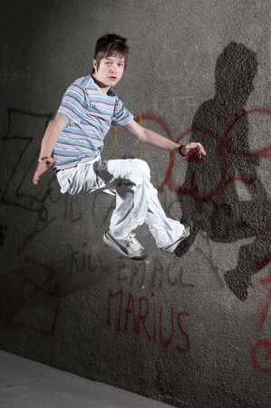 Jumping boy in front of a graffiti wall Stock Photo