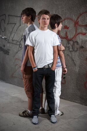 Three boy standing close in front of graffiti wall Stock Photo