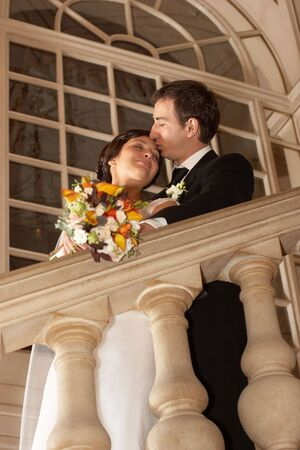 Groom embracing his bride on the theatre stairs photo