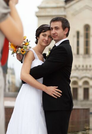 Young man and woman taking wedding photos in front of a cathedral
