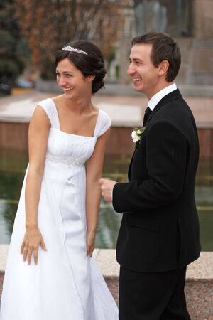 Young bride and groom smiling in front of camera photo