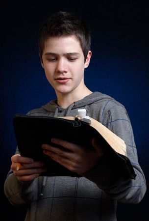 Young man reading and studying in his Bible