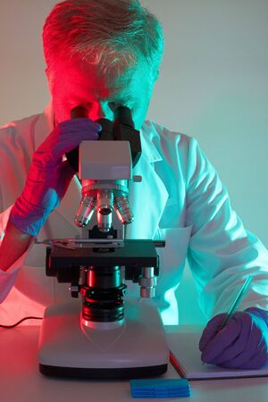 Medical professional scientist looking through a microscope Stock Photo - 5219259