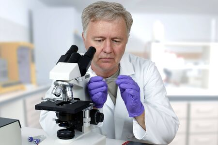 Researcher in the lab looking on microscope slide
