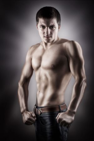 Handsome young guy showing his muscle on black lighted background photo