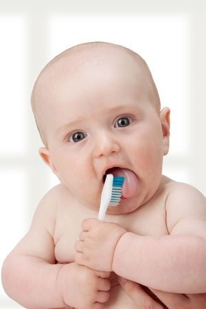 Baby boy playing with a new toothbrush