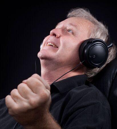 Happy senior listening something in his headphones photo