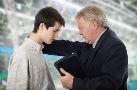 Preacher leading a young man in prayer to receive Lord Jesus