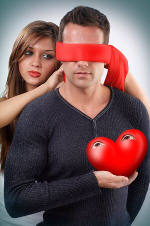 Woman blindfolding a man holding his open eyes heart in his hand  Stock Photo