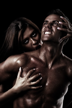 bit: Concept for painful sin. Young woman catching and possessing a young man in her spell  Stock Photo