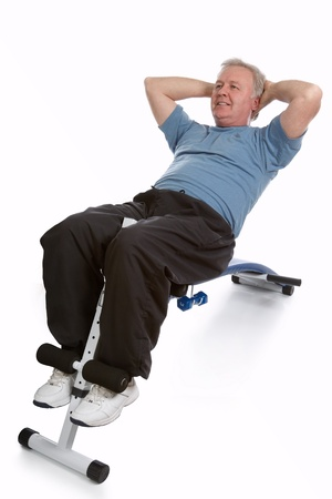 sit shape: Mature adult exercising his abdomen to stay in shape
