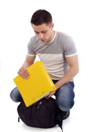 Young student packing his yellow notebook photo
