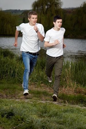 Fit men jogging outdoors beside the lake park